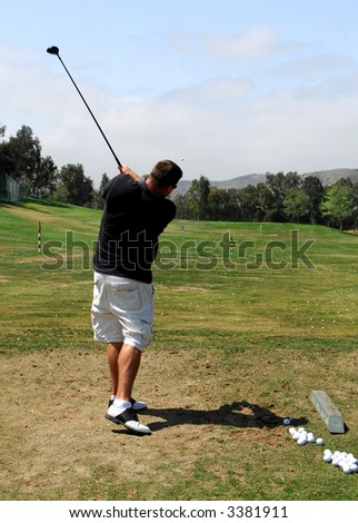 Man Practices at Golf Driving Range - stock photo