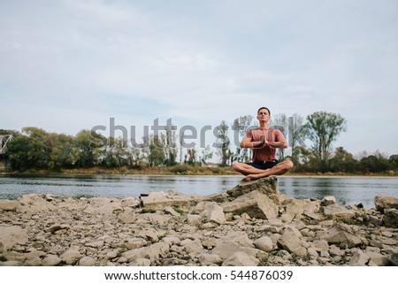 man practices yoga on the river bank