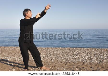Man practicing Tai Chi - Posture Raise Hands - stock photo