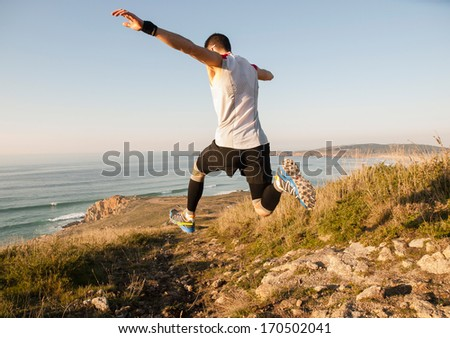 Man practicing trail running with a coastal landscape in the background - stock photo
