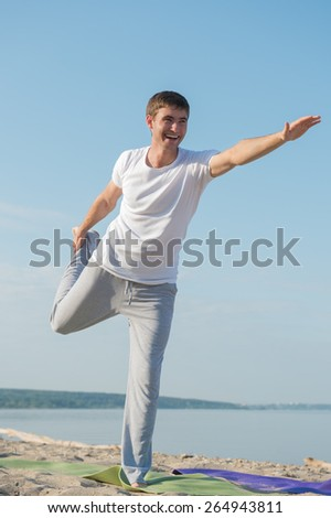 Man practicing yoga against a sea background - stock photo