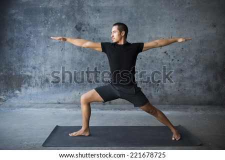 Man practicing yoga against a urban background - stock photo