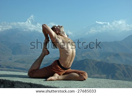 Man practicing yoga in Himalaya mountains, with view of Machapuchare, Nepal.