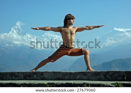 Man practicing yoga in Himalaya mountains, with view to Machapuchare, Nepal.