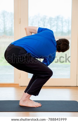 Man practicing yoga indoors in a retreat space doing Twisted Chair Pose - Parivrtta Utkatasana