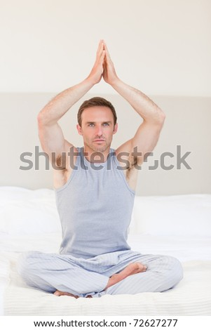 Man practicing yoga on his bed - stock photo