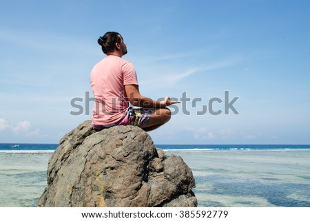 man practicing yoga sitting on a rock in front of the azure ocean. Stock image - stock photo
