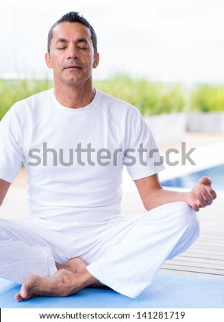Man practicing yoga sitting with his eyes closed
