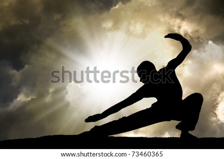 Man Practises Martial Arts with Dramatic Cloudy Sky in Background - stock photo