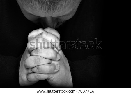 Man pray for something over black background with space for text on right