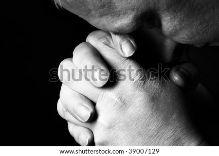 Man pray for something over the black background - stock photo