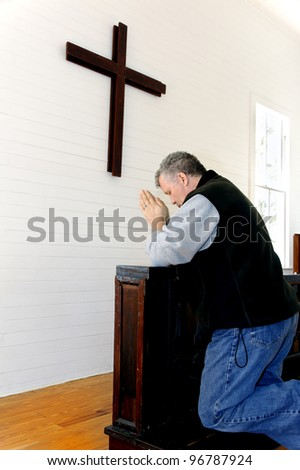 Man praying and kneeling in front of a simple wooden cross at a church. - stock photo