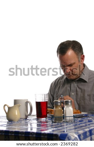 Man Praying at a table in Diner - stock photo