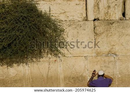 man praying at the western wall, jerusalem - stock photo