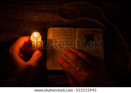 man praying on the Bible in the light candles selective focus - stock photo