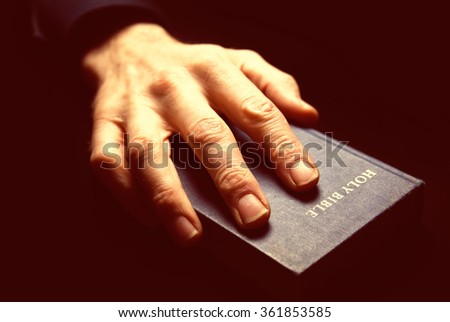 Man praying on the holy bible. The image has intentional added grain and styling. - stock photo