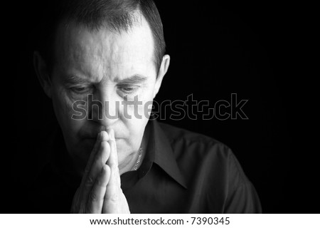 man praying or deep in thoughts, special black and white film-looking photo f/x - stock photo
