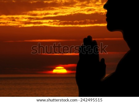 Man praying Outdoors. Nature. Sunset. - stock photo