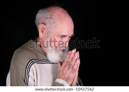 Man praying to God isolated on black background - stock photo