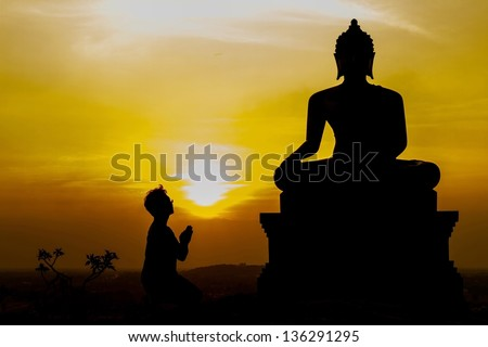 Man Praying To Statue Of Buddha at temple