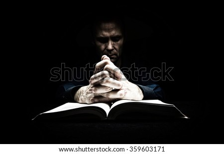 Man praying with his hands resting on the bible. The image has intentional added grain and styling. - stock photo