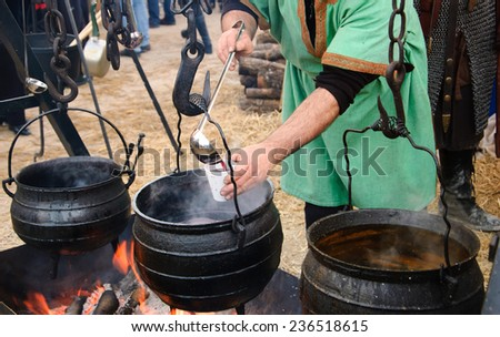 Man prepares and sells hot wine and soup at traditional Christmas Medieval fair in Provins (France).  - stock photo