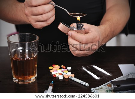 man prepares drug in spoon, close up - stock photo