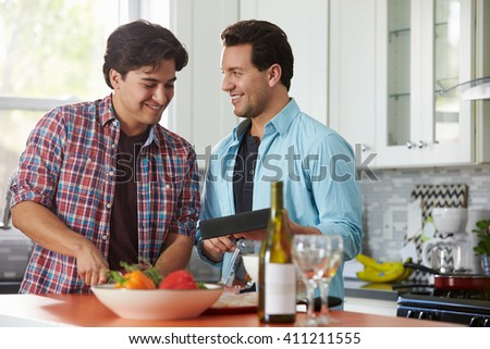 Man preparing a meal, his boyfriend holding a digital tablet - stock photo