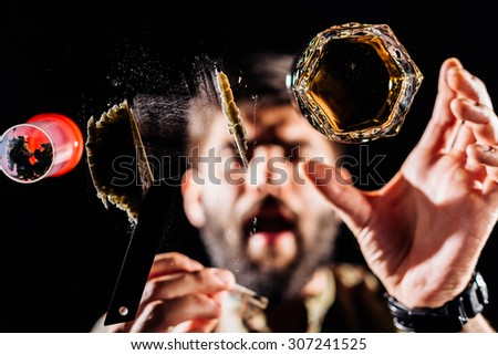 Man preparing a shot for snorting or sniffing cocaine lines on mirror with rolled banknote  - stock photo