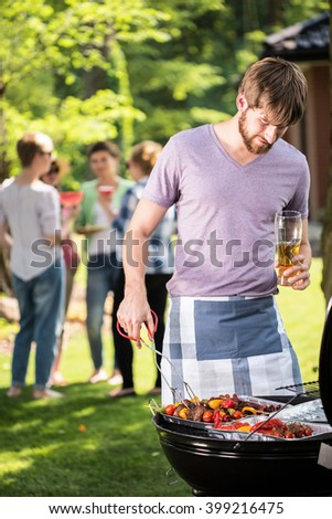 Man preparing food on garden barbecue with friends  - stock photo