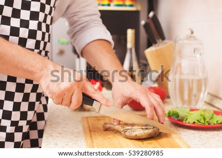 man preparing in the kitchen. knife cuts the chicken into pieces