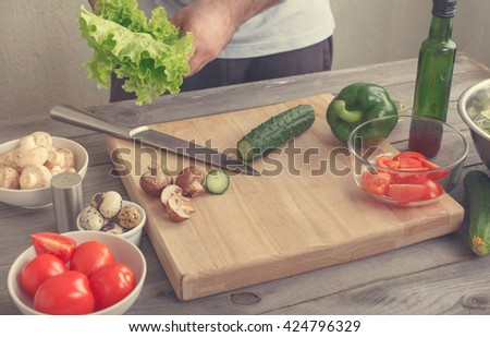 Man preparing of salad with fresh vegetables on a wooden table in rustic kitchen. Healthy food concept - stock photo