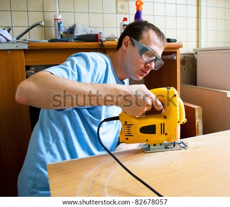 Man preparing to cut wood with a jigsaw - stock photo