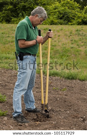 man preparing to erect a fence by digging a post hole
