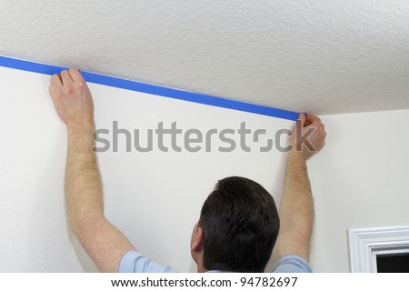 Man preparing to paint ceiling by masking off the wall beneath it with blue painter's tape. - stock photo