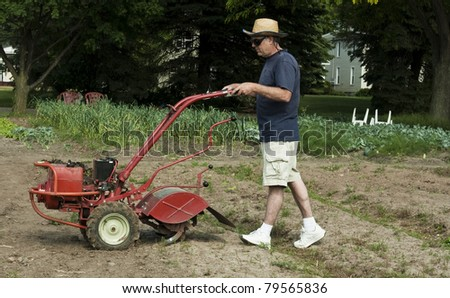 man preparing to till the soil in a garden - stock photo
