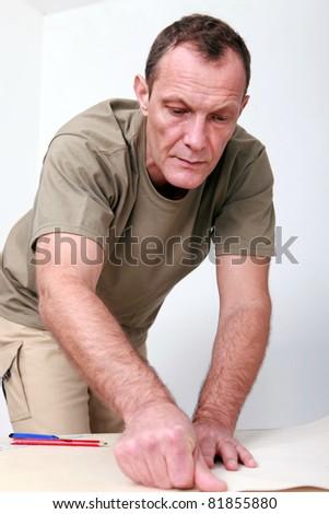 Man preparing wallpaper - stock photo