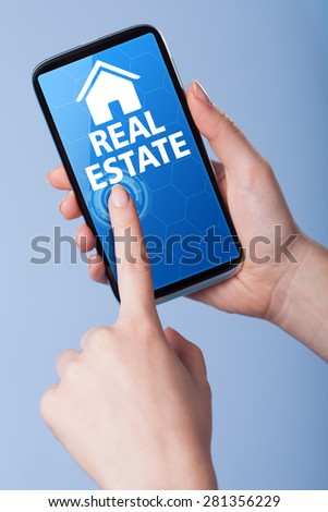 Man presses a touch screen smart phone with the symbol of real estate . Business, technology, internet concept. - stock photo
