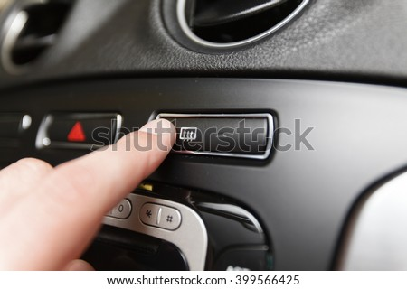 Man pressing button defrost (Shallow DOF).
