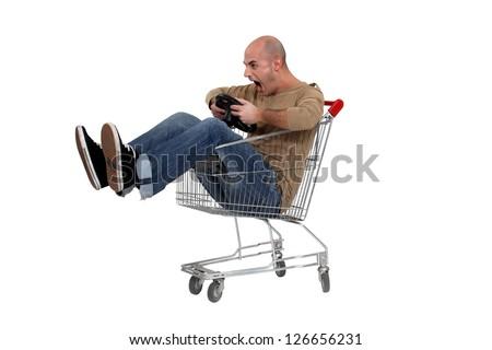 Man pretending to drive trolley - stock photo