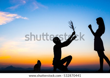 Man Proposing Engagement Silhouette Sunset Marriage Concept,Male giving female a flower.