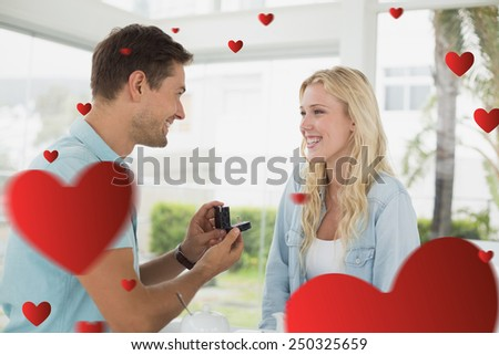 Man proposing marriage to his blonde girlfriend against hearts - stock photo