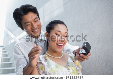 Man proposing marriage to his shocked girlfriend on the stairs - stock photo