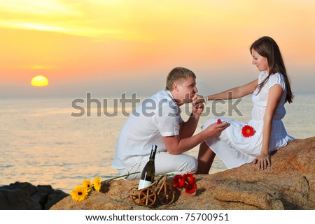 Man proposing to girlfriend and offering engagement ring - stock photo