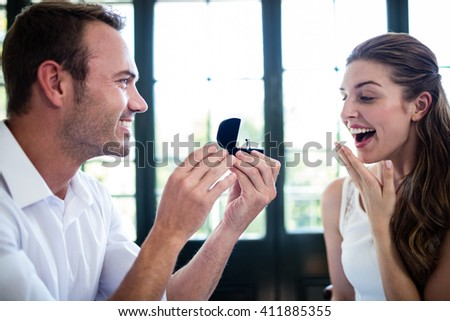 Man proposing to woman offering engagement ring in a restaurant - stock photo