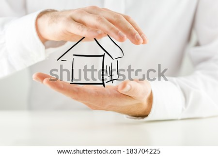Man protecting a hand sketched outline of a house with his hands conceptual of ownership, insurance, security and risk, closeup of his hands against his white shirt. - stock photo