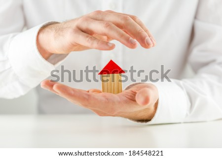 Man protecting a small wooden model house in his hands cupping it on his palm in a concept of ownership, investment, safety and security. - stock photo