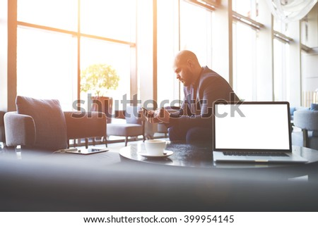 Man proud CEO is ordering on-line via cell telephone car for business trip, while is sitting in co-working cafe near table with open laptop computer with empty copy space screen for your advertising - stock photo