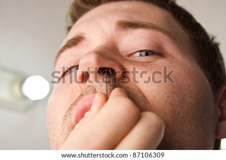 Man pucking nose hair with tweezers while facing camera - stock photo