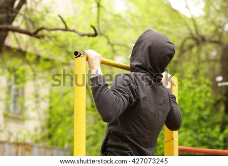 man pulled on a horizontal bar, exercise outdoors - stock photo